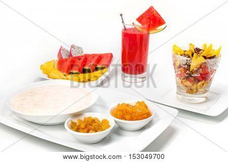 Bowl of porridge with raisins, and jam, glass of fresh exotic fruit exotic salad and sliced fruit, isolated on white.