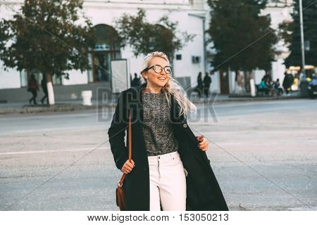 Blond woman wearing black coat, white pants, hipster glasses and holding brown leather handbag walking by road on city street in autumn. Fall casual fashion, elegant everyday look. Plus size model.