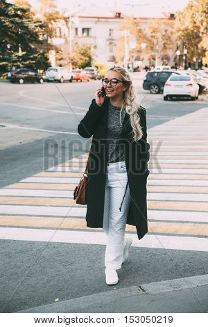 Blond woman wearing black coat, white pants, hipster glasses walking on the city street and talking by phone on crosswalk. Fall casual fashion, elegant everyday look. Plus size model, lifestyle photo.