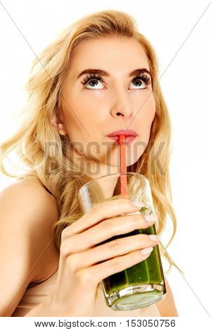 Young woman drinking green cocktail