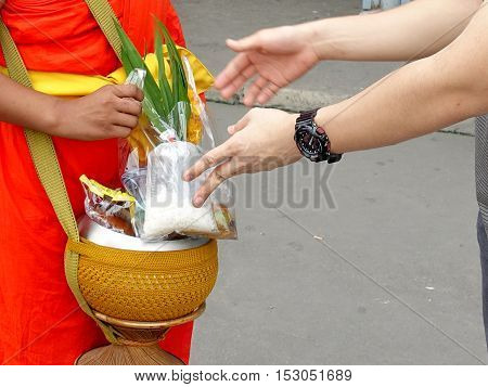 Buddhists make merit,Every morning Buddhist monk is given food offering from people for continuing ฺBuddhism. Selective focus.