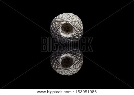 Front view of white ball of string isolated on black reflective background
