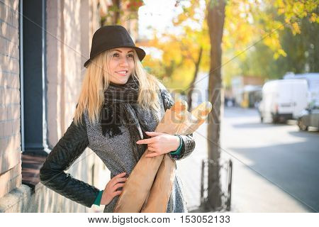 Young beautiful woman with a loaf of bread in her hands in autumn. Outdoors portrait.