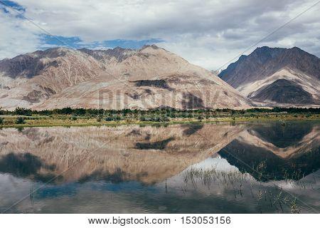 Mountain peaks reflect in water Nubra river