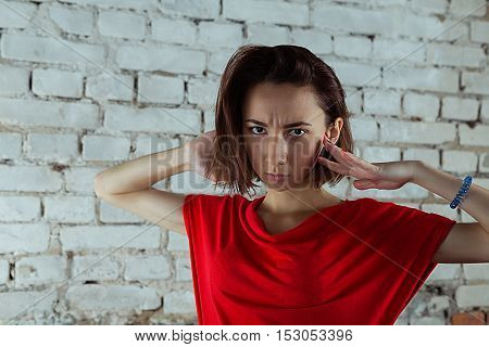 Photo with a serious girl standing against white brick wall