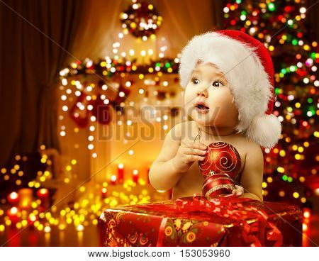 Christmas Baby Opening Present Happy Kid in Santa Hat Xmas Gift Box Child Looking Side
