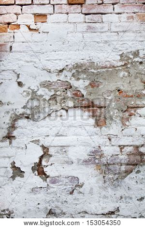 Chipped and peeling white paint on the surface of the old red brick wall. Cracked crumbled brown red grunge texture. Vintage background.