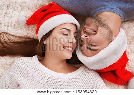 Young couple in Santa hats lying on fur carpet indoors