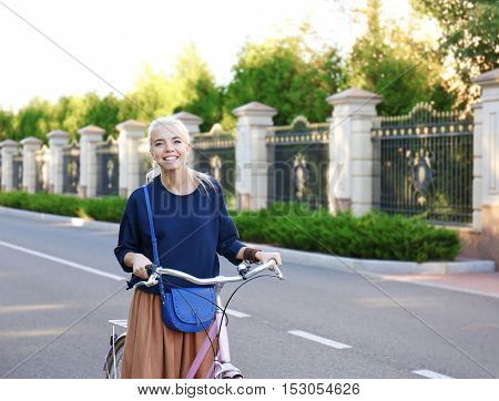 Pretty young woman with bicycle in park on blurred background