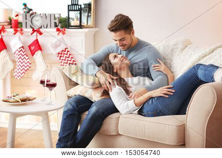 Young couple resting in room at Christmas time
