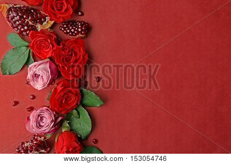 Composition of roses and pomegranate pieces on red background