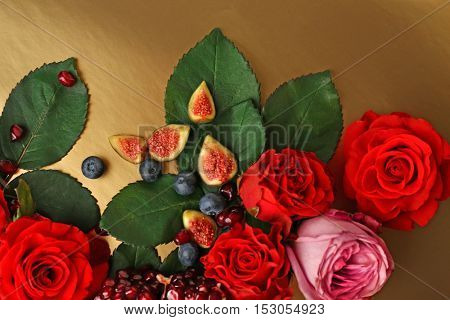 Composition of roses, figs, blueberries and pomegranate pieces on color background