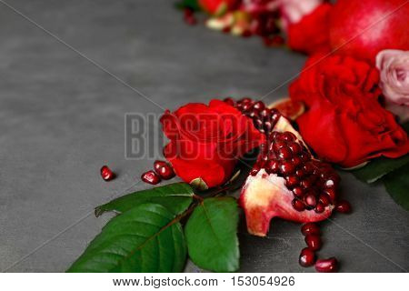 Composition of roses and pomegranate pieces on grey textured background