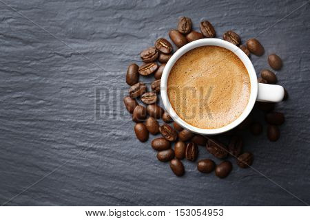 Roasted coffee beans with cup on color background