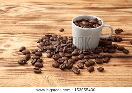 White cup with coffee beans on wooden background
