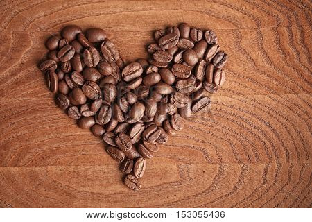 Heart formed by coffee beans on wooden background
