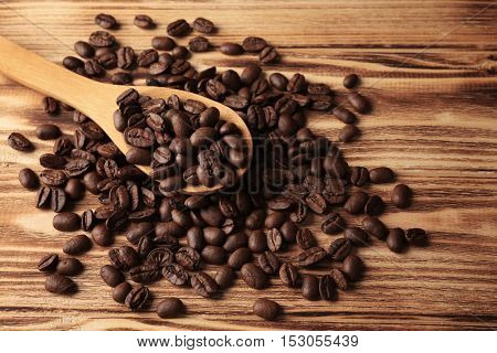 Spoon and coffee beans on wooden background