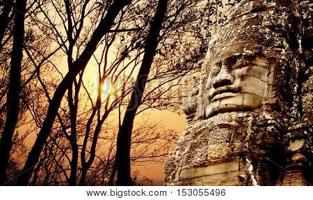 Giant stone face in Prasat Bayon Temple and trees on sunset sky background. Famous landmark Angkor Wat complex, khmer culture, Siem Reap, Cambodia