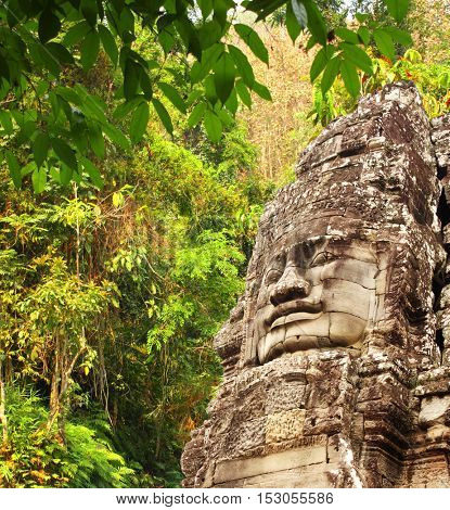 Giant stone face in Prasat Bayon Temple and trees in rainforest. Famous landmark Angkor Wat complex, khmer culture, Siem Reap, Cambodia