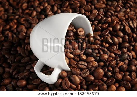 White cup and coffee beans, close up view