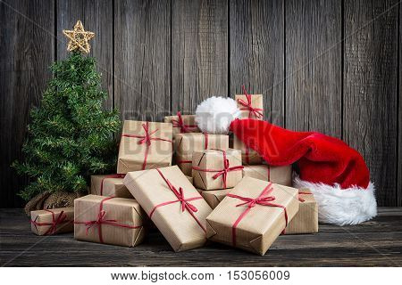 Vintage packages Christmas tree and Santa Hat against the background of the old wooden boards