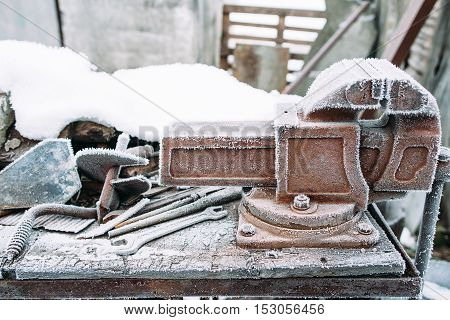 Frosted vise tool in outside workshop. Left outside tools in winter. Cold, early frosts, hoar concept