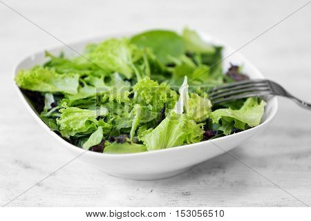 Fresh delicious salad on white wooden background, closeup
