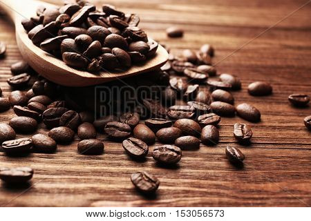 Wooden spoon and coffee beans on wooden background, close up view