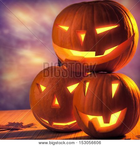 Halloween pumpkins still life, three carved gourds with glowing creepy faces on the table, traditional Halloween decor