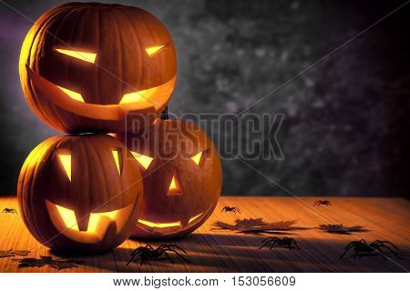 Halloween pumpkin still life, three carved gourds with glowing creepy faces on the table with many disgusting spiders, grunge holiday background with copy space
