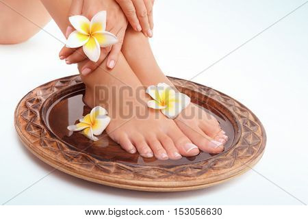 Closeup photo of a beautiful womens legs with perfect pedicure isolated on white blue background, doing spa procedures with water and flowers, beauty and health treatment concept