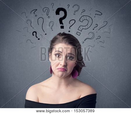 A pretty teenage girl standing confused in front of grey wall background with drawn question marks concept.