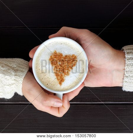 frothy cappuccino with heart symbol in hands top view / coffee break for two