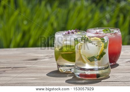 Three glasses of refreshing drink with herbs on a wooden table in the garden