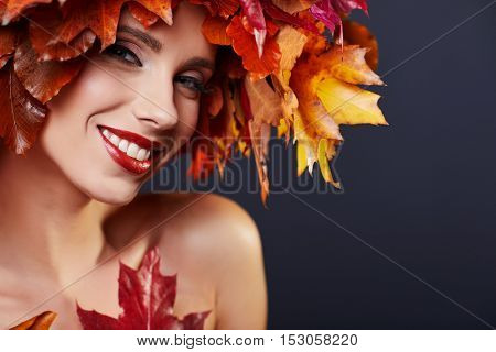 Woman with leafs on head in autumn concept.
