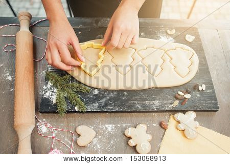 Christmas tree gingerbread cookies making. Female hands forming traditional xmas treat at kitchen. Homemade bakery, xmas sweet, winter holidays concept