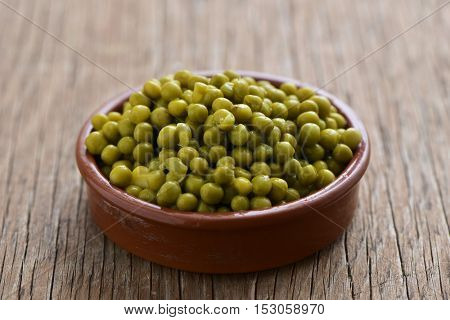 some cooked peas in an earthenware bowl, on a rustic wooden table