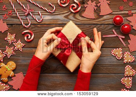 Female hands on christmas gift and homemade gingerbread cookie with handmade decoration on wooden background