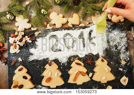 Confectioner remove 2016 sign on white flour. New year coming, winter holidays preparing. Cooking art