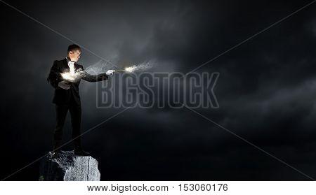 Businessman demonstrating magic . Mixed media