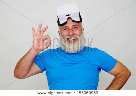 Man with white beard has just used virtual reality headset technology and is showing OK sign isolated against white background