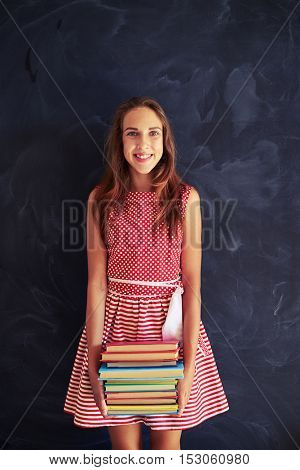 Pretty smiling teenage girl in dress is standing and holding a pile of books against school blackboard background