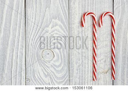 Christmas cane decoration on white wooden background