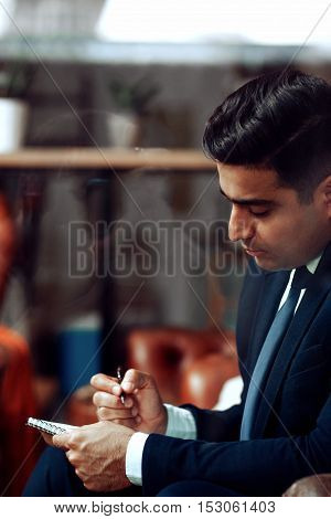 Foreign male student preparing for exams, free space. Studying at university and higher education concept.