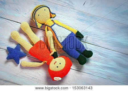 Crochet Toys Couple Laying On A Wooden Background With Copy Space For Your Text