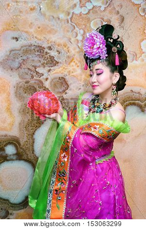 Sweet Chinese girl in violet traditional dress with flower against marble wall