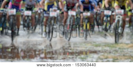 Large group of mountain bikers in rainy weather,blur image abstract