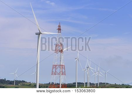 The big windmill turbine field and the electricity pylon with the blue sky