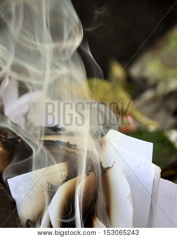 The process of burning paper. A stack of burnt paper with smoke and ash. Close-up. Vertical view.