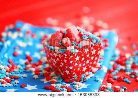 Delicious candies and sprinkles in paper box on napkin